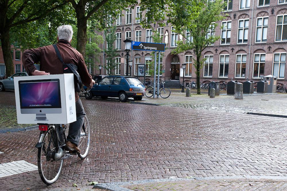 Een man fietst met een net aangeschafte Apple iMac.<br /> <br /> A man is bringing his new iMac home by bike