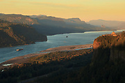 Barge passing beneath Vista House on the Columbia Gorge at sunset, Oregon.