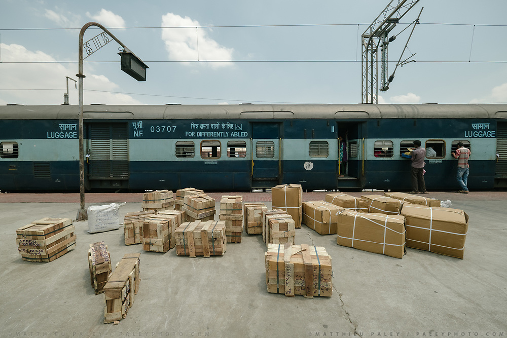 A cluster of packages sits on the platform, waiting to be loaded into the luggage compartment. Outside the Dibrugarh-Kanyakumari Vivek Express, the longest train route in the Indian Subcontinent. It joins Kanyakumari, Tamil Nadu, which is the southernmost tip of mainland India to Dibrugarh in Assam province, near the border with Burma.