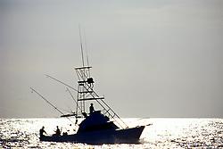 sport fishing boat, trolling at sunset, Kona, Big Island, Hawaii