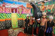 Hos en fotograf poserar barn framför en modell av templet i Sabarimala. Hinduiska pilgrimer, på väg till det heliga templet i Sabarimala, dansar på gatorna i den indiska staden Erumely i Kerala. För att helt uppgå i pilgrimsvandringen, ge upp sitt eget ego och för att hedra Lord Ayyappa, målar pilgrimerna sina kroppar och bär vapen i trä. Traditionen kallas pettatullal. Både hinduer och muslimer anser att Erumely är en helig stad.  <br /> <br /> Children at a photostudio are posing in front of a model of the temple in Sabarimala. Sabarimala pilgrims are dancing on the streets of Erumely in the Kottayam district of Kerala, India. In order to give up their egos and to surrender to Lord Ayyappa, the Hindu pilgrims paint their bodies and carry weapons made of wood on the way to Sabarimala. Erumely is considered holy by both Hindus and Muslims.<br /> <br /> Copyright 2016 Christina Sjögren, All Rights Reserved
