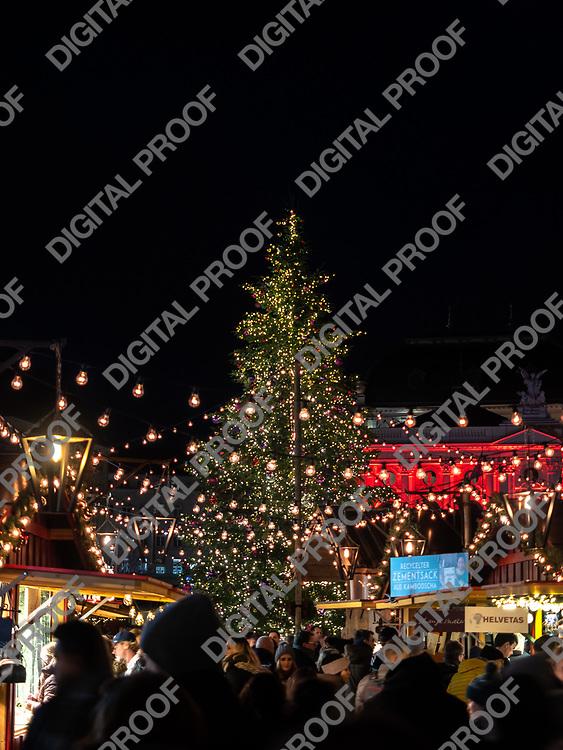 Zurich, Switzerland - December 22, 2018 Natural christmas tree and vendor stands with visitors at Christmas market held at Sechseläutenplatz