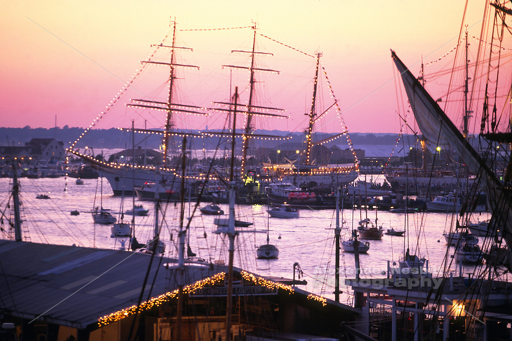 USA, Newport, RI- Rooftop view of Bowen's Wharf, Bannister's Wharf, the Tall Ship Rose, and Newport Harbor at sunset in summertime during the 2000 tallships festival.