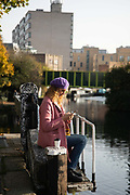 A woman checks her phone on the third day of the second coronavirus national lockdown by the Regents Canal on 7th of November 2020, East London, United Kingdom. The lockdown restrictions mean that people are only allowed to meet outside, in pairs and only if keeping social distance.