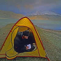 CHINA, Xinjiang Province. Mark Newcomb (MR) writes in his journal in camp by Lake Karakul in Pamir Mountains.