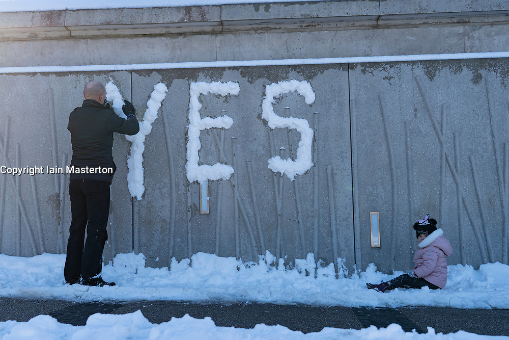 """Edinburgh, Scotland, UK. 12 Feb 2021.  As the cold weather continues members of the public are out in Holyrood Park playing sport and making political slogans. Pic;  A man makes a Pro- Scottish Independence  """"Yes"""" slogan from snow on the walls of The Scottish Parliament building at Holyrood. Iain Masterton/Alamy Live news"""
