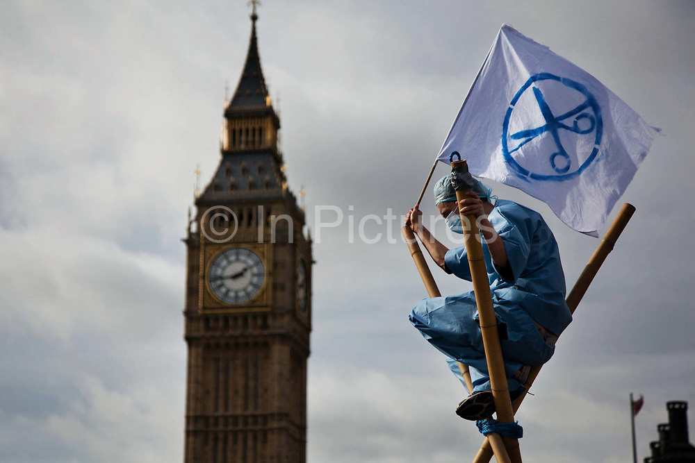 The bridge was blocked using two tripods carrying a banner with people on each tri-pod. A man dressed as a health worker carrying a UK Uncut flag.<br /> The Health and Care Bill has been passed by Parliament and is due to go to the House of Lords. In protest against the bill which aim to deconstruct and privatise large parts of the NHS UK Uncut activists together with health workers and trade unionists blocked the Westminster Bridge from 1pm til 5.30pm.