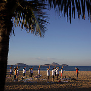 An early morning fitness class on Ipanema Beach, Rio de Janeiro,  Brazil. 12th July 2010. Photo Tim Clayton..The beaches of Rio de Janeiro, provide the ultimate playground for locals and tourists alike. Beach activity is in abundance as beach volley ball, football and a hybrid of the two, foot volley, are played day and night along the length and breadth of Rio's beaches. .Volleyball nets and football posts stretch along the cities coastline and are a hive of activity particularly at it's most famous beaches Copacabana and Ipanema. .The warm waters of the Atlantic Ocean provide the ideal conditions for a variety of water sports. Walkways along the edge of the beaches along with exercise stations and cycleways encourage sporting activity, even an outdoor gym is available at the Parque Do Arpoador overlooking the ocean. .On Sunday's the main roads along the beaches of Copacabana, Leblon and Ipanema are closed to traffic bringing out thousands of people of all ages to walk, run, jog, ride, skateboard and cycle more than 10 km of beachside roadway. .This sports mad city is about to become a worldwide sporting focus as they play host to the world's biggest sporting events with Brazil hosting the next Fifa World Cup in 2014 and Rio de Janeiro hosting the Olympic Games in 2016...