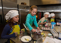 Allison Ellis with Kendall Madon and Maddy Isabelle with Avery Totten add chocolate chips to their chocolate chip banana muffin batter during Cooking Class at the Gilford Youth Center on Tuesday afternoon.  (Karen Bobotas/for the Laconia Daily Sun)