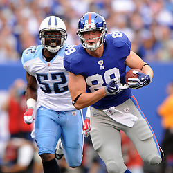 Tight End Kevin Boss #89 of the New York Giants runs ahead of linebacker Jamie Winborn #52 of the Tennessee Titans after a reception during first half NFL football action between the New York Giants and Tennessee Titans at New Meadowlands Stadium in East Rutherford, New Jersey. The game is tied at half time.