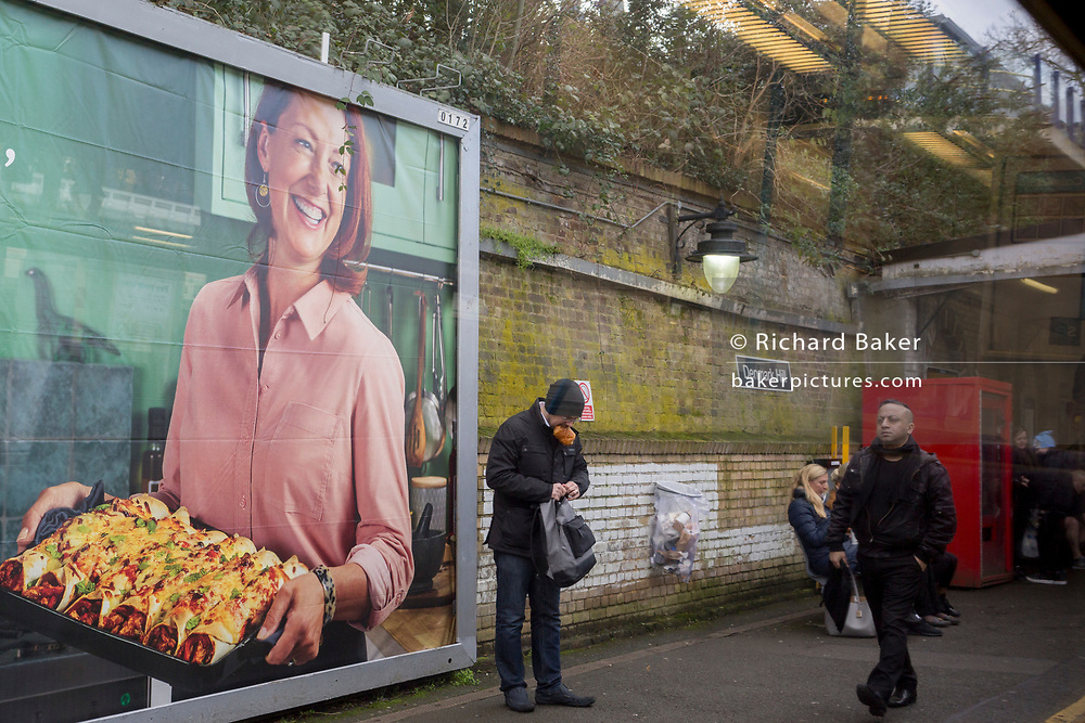 A rail passenger momentarily holds a sandwich in his mouth beneath an advertising billboard for home baked spicy wraps, on the platform at Denmark Hill rail station, on 14th February 2020, in London, England.