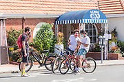Young Adults On Bikes Wearing Face Masks In Front of Las Brisas Restaurant