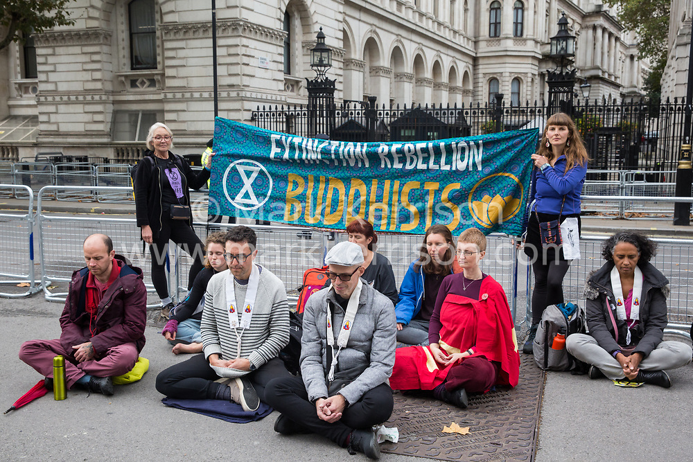 London, UK. 8 October, 2019. Climate activists from Extinction Rebellion Buddhists meditate in Whitehall outside Downing Street on the second day of International Rebellion protests to demand a government declaration of a climate and ecological emergency, a commitment to halting biodiversity loss and net zero carbon emissions by 2025 and for the government to create and be led by the decisions of a Citizens' Assembly on climate and ecological justice.