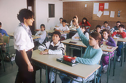 School classroom scene in Barcelona with teacher standing at front of class and pupil holding hand up to ask a question,