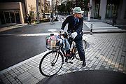 TOKYO, JAPAN, 9 APRIL - A old man on a bicycle with a green cap and watching to the right. The dog in the basket watch in the same way. April 2012 [FR] un vieil homme sur son velo portant une casquette verte regarde sur la droite. Son chien dans le panier avant regarde dans la même direction.