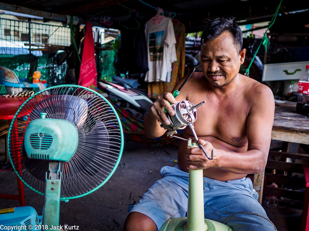 17 DECEMBER 2018 - BANGKOK, THAILAND: A man repairs electic fans under a highway overpass near the Sukhumvit Road tourist district in central Bangkok. According to Credit Suisse Global Wealth Databook 2018, which surveyed 40 countries, Thailand has the highest rate of income inequality in the world. In 2016, Thailand was third, behind Russia and India. In 2016, the 1% richest Thais (about 500,000 people) owned 58.0% of the Thailand's wealth. In 2018, they controlled 66.9%. In Russia, those numbers went from 78% in 2016, down to 57.1% in 2018. The Thai government disagreed with the report and said the report didn't take government anti-poverty programs into account and that Thailand was held to an unfair standard because most of the other countries in the report are developed countries in the Organisation for Economic Co-operation and Development.    PHOTO BY JACK KURTZ