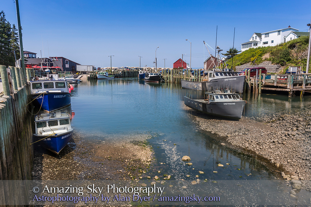 A composite of the low and high tide positions of the water and boats at Halls Harbour, Nova Scotia on August 17, 2015. Taken from the first and last frames of a time-lapse sequence. The foreground is from low tide, with the harbour bottom exposed and the boats on the bare ground. The top is from high tide with the boats now floating much higher.