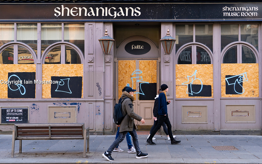 Glasgow, Scotland, UK. 23 March 2021. On the first anniversary of the coronavirus pandemic lockdown the streets in Glasgow city centre are still quiet with only essential shops open. Pic; Closed and boarded up bar on Sauchiehall Street.  Iain Masterton/Alamy Live News
