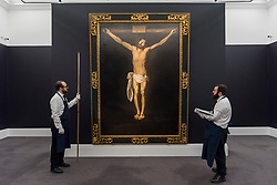 """© Licensed to London News Pictures. 29/11/2019. LONDON, UK. Technicians inspect """"Christ on the Cross"""", circa 1635-40, by Francisco de Zurbaran (Est. GBP2.5-5.0m) at the preview of Old Masters sales at Sotheby's, New Bond Street.  Works will be offered for sale on 4 and 5 December.  Photo credit: Stephen Chung/LNP"""