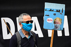 "© Licensed to London News Pictures. 06/09/2020. LONDON, UK.  An activist from Extinction Rebellion (XR) with a sign takes part in a ""Flood Alert"" protest on the shore of the River Thames near Gabriel's Wharf on the South Bank to highlight the effects of climate change on rising sea levels.  Photo credit: Stephen Chung/LNP"