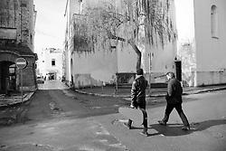 Due persone si recano nella piazza centrale di Racale, una porta uno strumento musicale con sè.