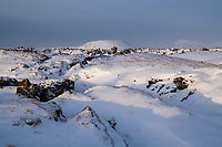 Búðir lava field in winter, snow covering ground and mountains in background. Snæfellsnes Peninsula, West Iceland.
