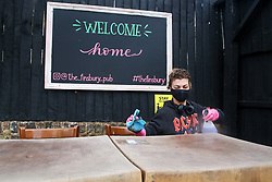 © Licensed to London News Pictures. 08/04/2021. London, UK. A member of staff cleans as table in the 'secret beer garden' at The Finsbury Pub in Finsbury Park, north London with 'Welcome Home' sign in the background, as pubs with beer gardens prepare to re-open on Monday 12 April, following the easing of Covid-19 lockdown restrictions. Photo credit: Dinendra Haria/LNP