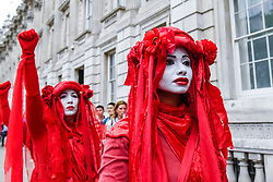 © Licensed to London News Pictures. 16/09/2019. LONDON, UK.  Members of the Invisible Circus, commonly associated with climate change group Extinction Rebellion, walk silently down Whitehall joining anti-Brexit protesters, the day before the Supreme Court is to begin a three-day hearing to decide whether or not the decision of Prime Minister Boris Johnson to prorogue Parliament is unlawful.  Photo credit: Stephen Chung/LNP