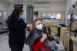 © Licensed to London News Pictures. 12/04/2021. London, UK. A woman gestures as she gets her hair cut in a beauty salon on Green Lanes in Haringey, north London, which reopens after 4 months of Covid-19 lockdown. Cafes, restaurants, pubs, non-retail business and hairdressers across the UK closed following third national lockdown on 6 January, after a surge of coronavirus infections and hospital admissions across the UK. As restrictions are eased, cafes, restaurants, pubs, non-retail business and hairdressers reopen today.<br /> Photo credit: Dinendra Haria/LNP