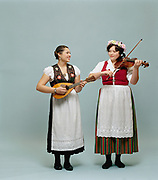 Two young female musicians posing with instruments for in studio portrait.