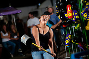 High Striker strongman game participant laughing at the Northwest Montana Fair in Kalispell, Montana.