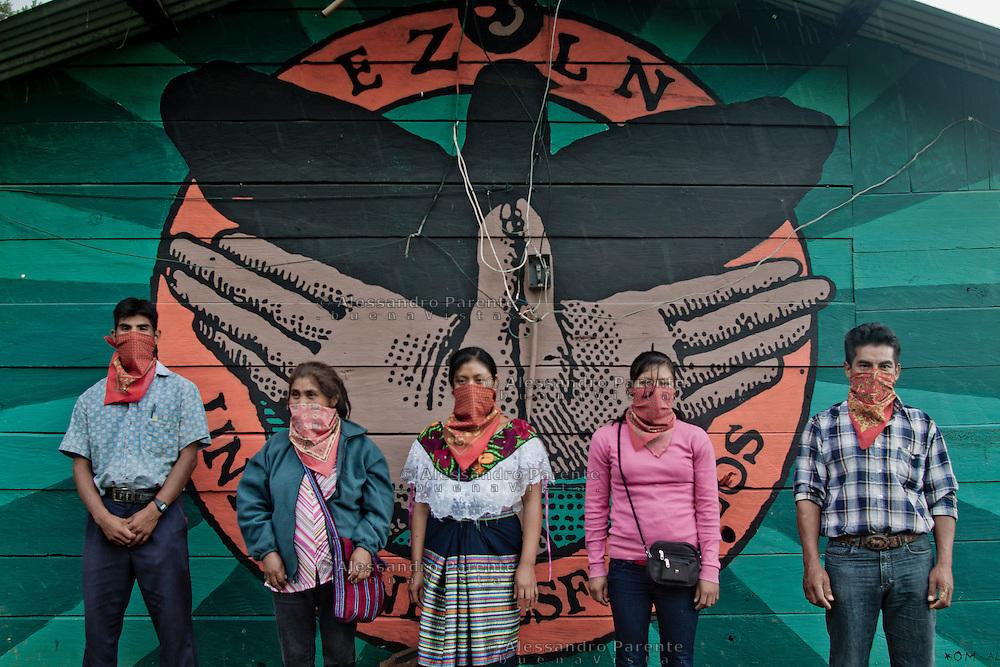 """A group of zapatists is posing in front of """"gran om"""" murales.<br /> Un grupo de zapatistas posando adelante de un murales de """"gran om""""."""