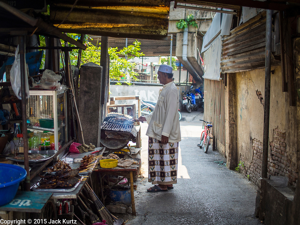 10 APRIL 2015 - BANGKOK, THAILAND:  A Thai Muslim man grills fish at a street food stall in the Thonburi section of Bangkok. A Pew Research Center study recently released identified Islam as the fastest growing religion in the world.   PHOTO BY JACK KURTZ