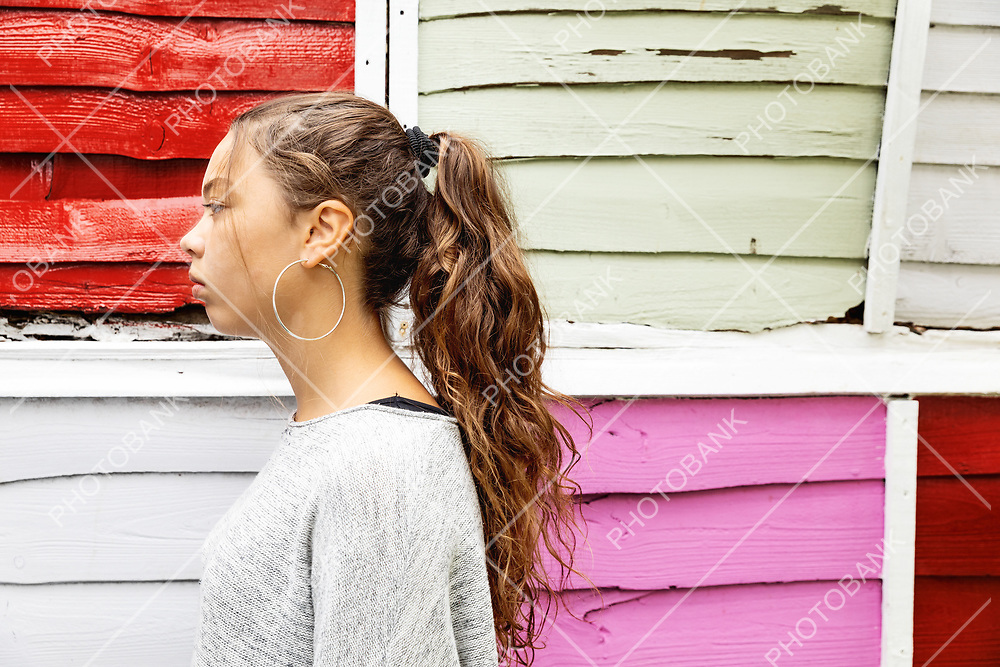 Profile portrait of a girl with colored fence behind. Frontal view. Nobody inside