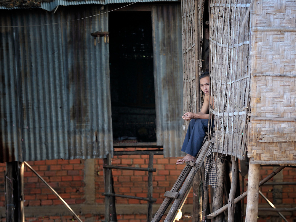 A man sitting in the door of his home in the Chamroen neighborhood of Phnom Penh, Cambodia.