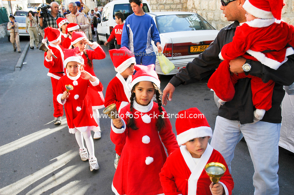 Israel, Haifa, Wadi Nisnas, Children dressed up as Santa Claus in a parade during the Holiday of holidays festival, celebrating Hanuka-Christmas-Ramadan December 2006