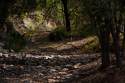 Dry streambed that feeds Lake Travis in the Hill Country of Texas during drought.