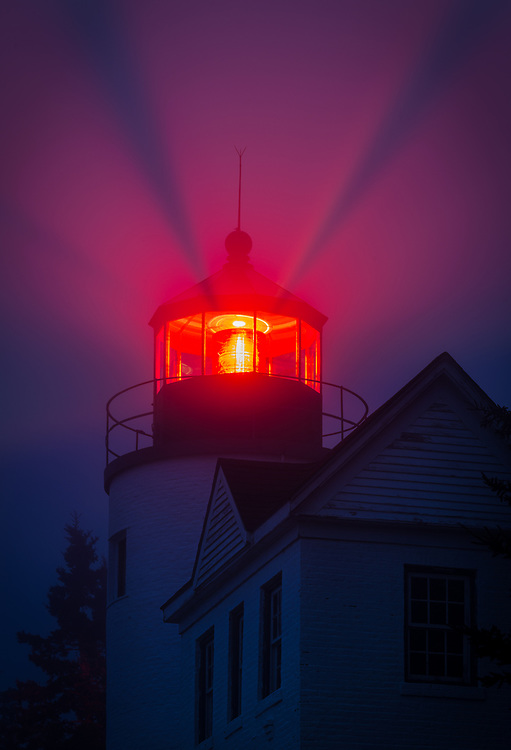 The red light from Bass Harbor Lighthouse shines through fog, Acadia National Park, Maine
