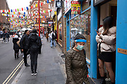 As Londoners await the announcement of a second coronavirus lockdown it's business as usual in the West End with people out and about on what will be the last weekend before a month-long total lockdown, as seen here in Chinatown with people in face masks passing a woman texting from the doorway of a massage shop on 30th October 2020 in London, United Kingdom. The three tier system in the UK has not worked sufficiently, to suppress the virus, and there have have been calls by politicians for a 'circuit breaker' complete lockdown to be announced to help the growing spread of the Covid-19.