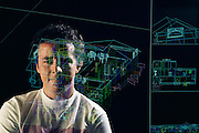 Virtual reality. Harry Marples, Computer Scientist, programming a system that will allow visitors a 3-D guided tour of a new building before it is even built. Plans for a proposed design are fed into a computer, which is capable of displaying them in sophisticated 3-D graphics. Thus the real building is presented by the computer as a virtual one. Visitors wearing special headsets fitted with video goggles and spatial sensors can move from room to room within the virtual space as if they were in the real world. Optical fibers woven into rubber data gloves provide a tactile dimension. Photo taken at the Computer Science Dept., University of North Carolina. Model Released (1990)