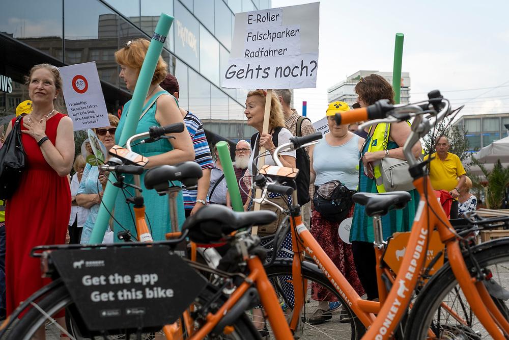 An die hundert Menschen protestieren in Berlin auf einer Demonstration des Fachverband Fußverkehr Deutschland (FUSS) für die Rechte von Fußgängern, für freie Gehwege und gegen Falschparker und gegen Fahrräder und E-Tretroller, die auf Gehwegen fahren und stehen und liegen. Demonstrantin mit Schild: E-Roller Falschparker Radfahrer - Geht's noch?<br /> <br /> [© Christian Mang - Veroeffentlichung nur gg. Honorar (zzgl. MwSt.), Urhebervermerk und Beleg. Nur für redaktionelle Nutzung - Publication only with licence fee payment, copyright notice and voucher copy. For editorial use only - No model release. No property release. Kontakt: mail@christianmang.com.]