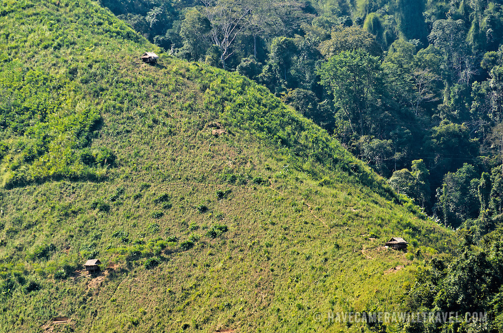 Rice fields in the mountaineous terrain of Luang Namtha province in northern Laos. Small bamboo huts on the mountainside provide shelter to the farm laborers while they tend their crops and during the harvest.