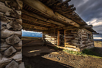 Cunningham Cabin in Grand Teton National Park looking out towards the Teton Mountain Range at sunset.
