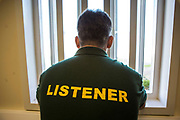 A prisoner wearing a listener t-shirt looks out of a cell window. <br /> HMP/YOI Portland, a resettlement prison with a capacity for 530 prisoners. Dorset, United Kingdom.