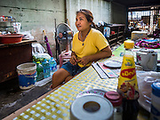 02 SEPTEMBER 2015 - BANGKOK, THAILAND: A woman in an abandoned building that has been temporarily turned into a coffee stand in Bang Chak Market. When demolition crews come to the building the coffee stand will close. The Bang Chak Market serves the community around Sois 91-97 on Sukhumvit Road in the Bangkok suburbs. About half of the market has been torn down, vendors in the remaining part of the market said they expect to be evicted by the end of the year. The old market, and many of the small working class shophouses and apartments near the market are being being torn down. People who live in the area said condominiums are being built on the land.         PHOTO BY JACK KURTZ