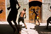 Boys playing football on the streets of favela Jacarezinho, Rio de janeiro, Brazil