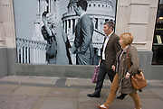 A couple walk past a fashion poster showing a fashion boy and girl and St Paul's Cathedral.
