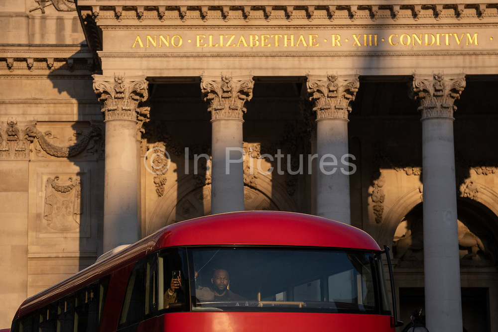 Latin inscriptions on the pediment of the Royal Exchange Passengers look from the front seats of their London bus in the City of London, the capitals financial district, on 27th February 2021, in London, England. At the top of Doric and Ionic columns with their ornate stonework, powerfully strong lintels cross, bearing the load of fine artistry and carvings which feature the design by Sir William Tite in 1842-1844 and opened in 1844 by Queen Victoria whose name is written in Latin Victoriae R. It's the third building of the kind erected on the same site. The first Exchange erected in 1564-70 by sir Thomas Gresham but was destroyed in the great fire of 1666. It's successor, by Jarman, was also burned down in 1838. The present building is grade 1 listed and cost about £150,000.