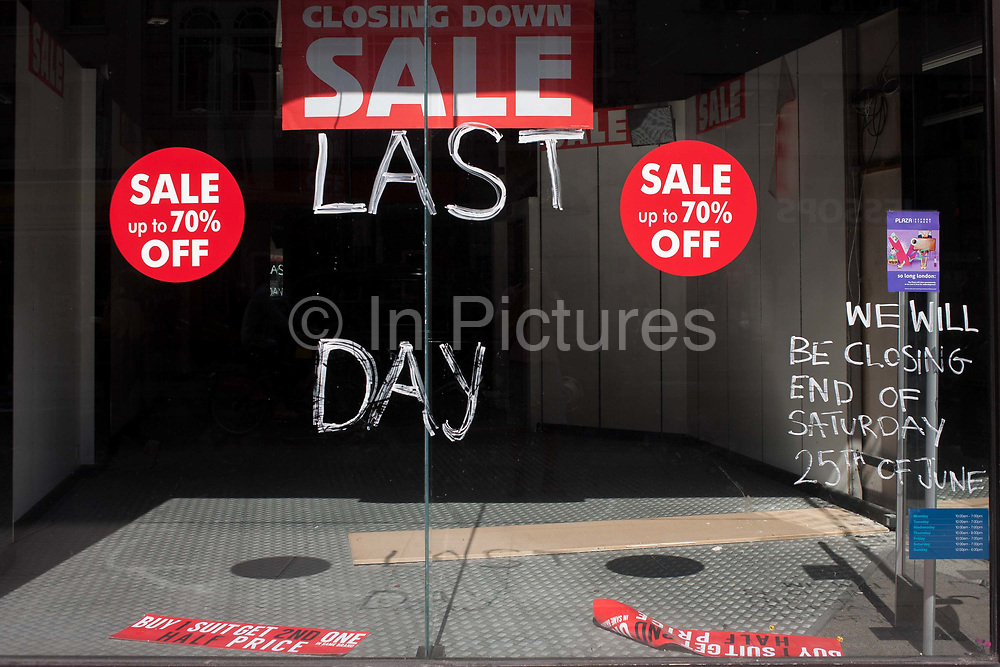 The window of a now vacant shop business window, closed after its last day of trading in Oxford Street, on 24th August 2016, London, UK. The words Last Day has been painted on the glass and whose shadows are seen on the floor of the former retailer.