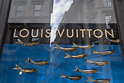Luxury accessories brand, Louis Vuittons logo and window design featuring golden swimming fish is seen in the window of the companys Cornhill premises, on 21st August 2020, in London, England.